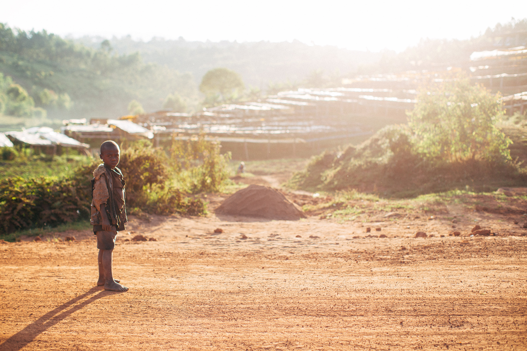 Drenched in equatorial light, one of the Carlson's young neighbors stands in front of the Long Miles washing station in Bukeye, Burundi.
