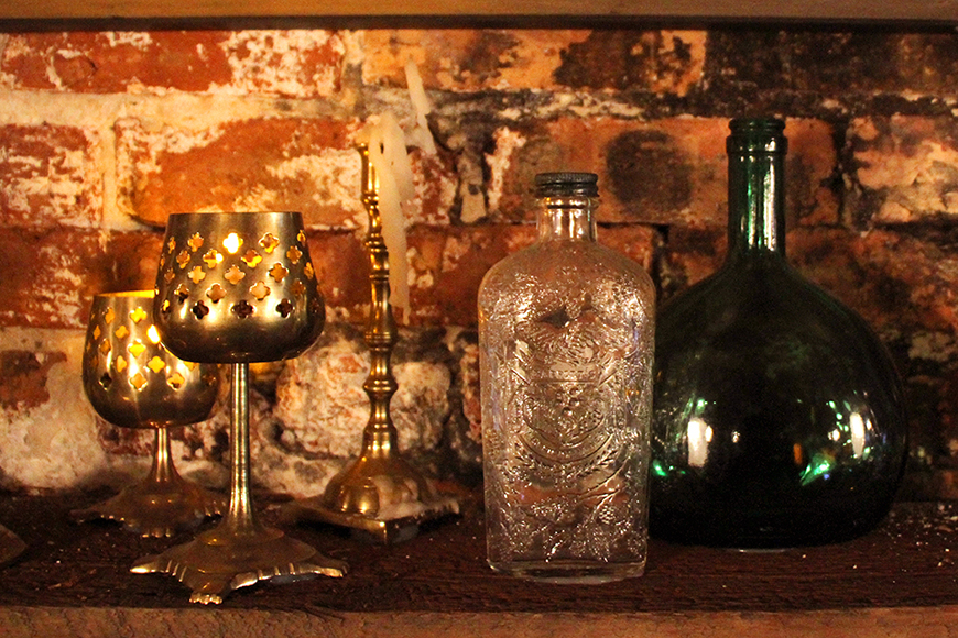 Vintage bottles of rum and other seafaring paraphernalia line the wall shelves. Photo by Emma Janzen.