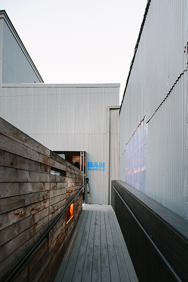 The walkway to Bar Agricole's entrance is marked by corrugated steel, glass and reclaimed wood.