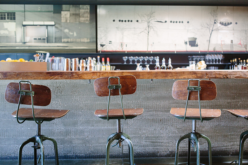 Concrete and industrial-style stools help define the bar area.
