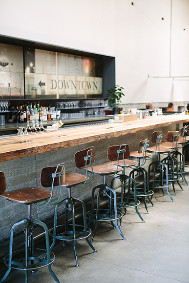 A long, wooden bar top adds warmth to the bar area.