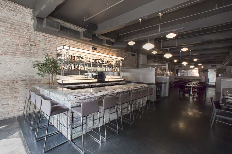 The main bar at Rebelle is marked by a marble bartop and muted color scheme.