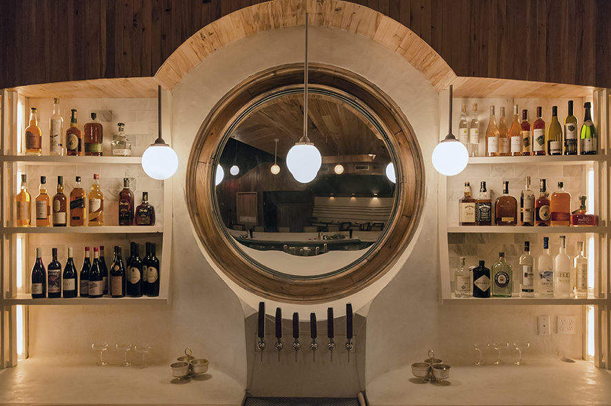 Warm lighting and an otherworldly circular mirror define the bar space at Sisters.