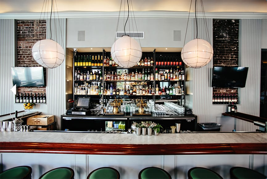 The bar spans a large portion of the main dining room, decorated with hand-blown fixtures that evoke maritime lighting.