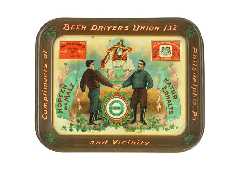 "A beer tray that dates to about 1905 shows a beer truck driver and brewer working together in a show of solidarity. The text says, in German, ""Liberty, Equality, Fraternity."""