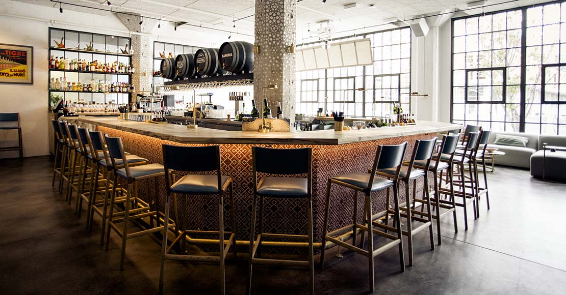 Huge industrial windows flood the bar area with fresh natural light at Bellota in San Francisco.