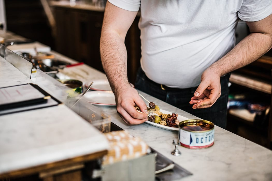 Hands-doing-stuff sometimes show as much character as faces. This is Mikey Nicolian preparing Continental Deli's tinned seafood plate.