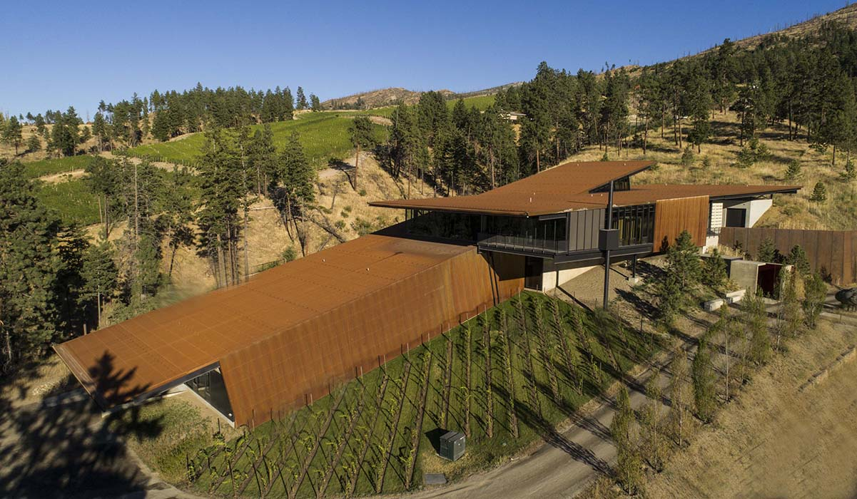 The steel-clad building juts out from the hill in two different directions to accommodate a gravity flow winemaking system and views from the top floor tasting room. | Photo by Nic Lehoux.