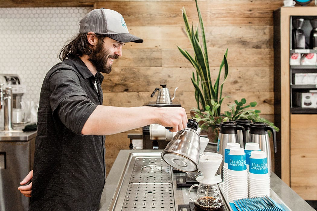 Garrett Henry works the pour-over station at Blueprint Coffee. | Photo by Jennifer Silverberg.