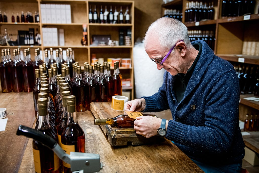 Bottles of Armagnac being hand-labeled at Darroze, a prominent negociant.