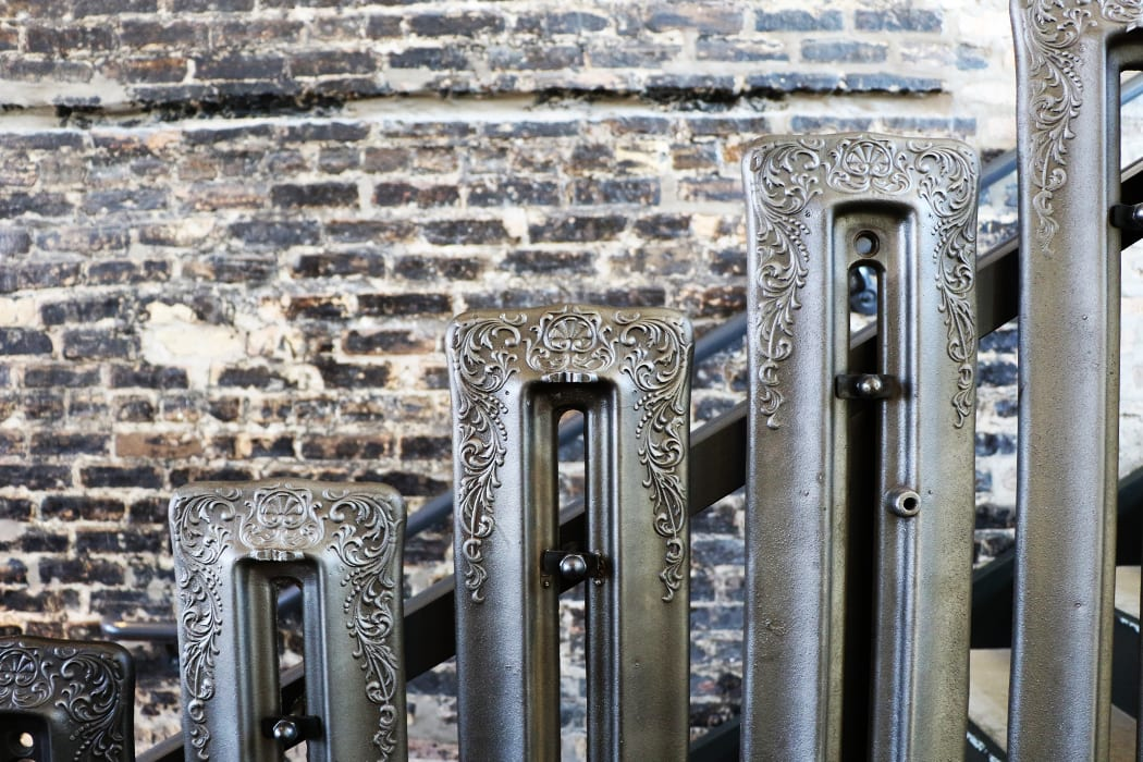Many details from the original building were restored and repurposed, like these old radiators that now make up the staircase railing. | Photo by Emma Janzen.