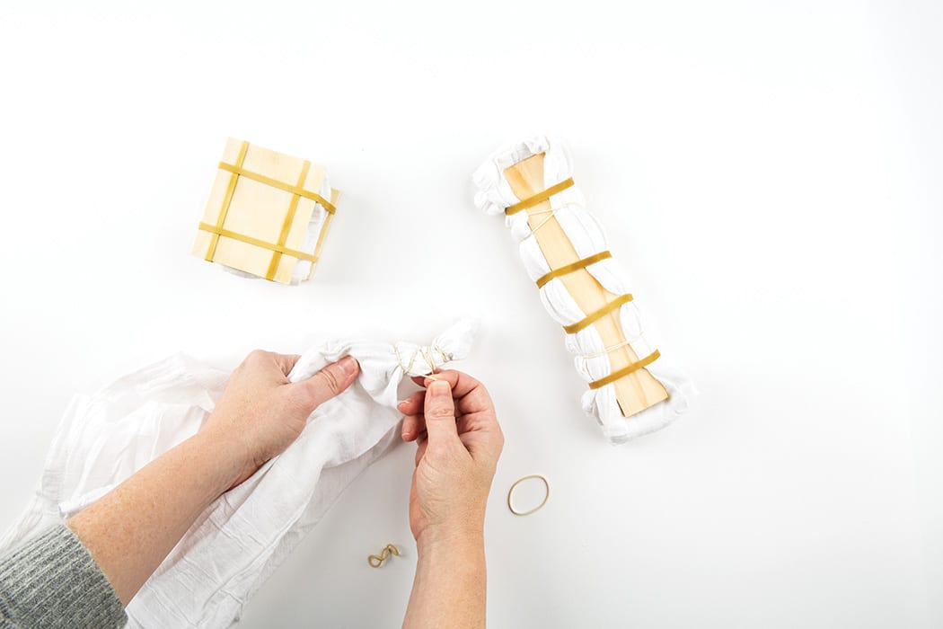 Using rubber bands, kitchen twine, wood blocks or chopsticks, fold and bind the towels (see above for design ideas).