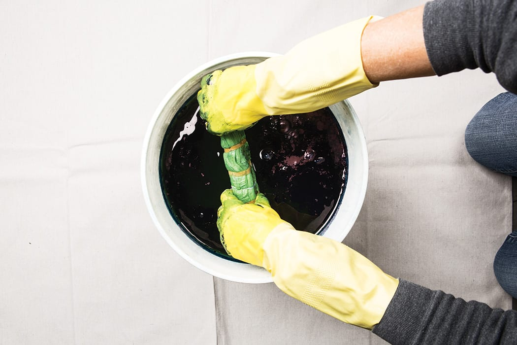 Wet the towels in water and squeeze out excess water. Wearing gloves and using a wooden spoon or stir stick, push the bloom to the side. Squeeze your towel and slowly submerge it into the dye bucket. While submerged, move the towel around in your hand for 1 to 2 minutes to be sure the dye also penetrates the folded parts.