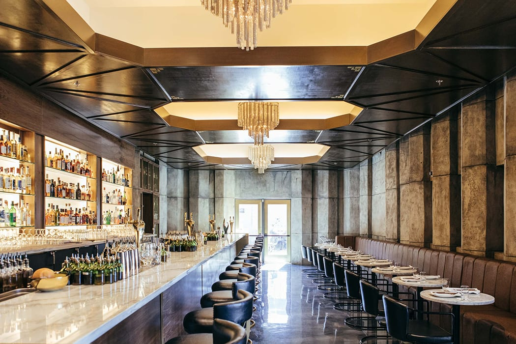 In the main restaurant and bar space, undulating concrete walls contrast glittering glass chandeliers.